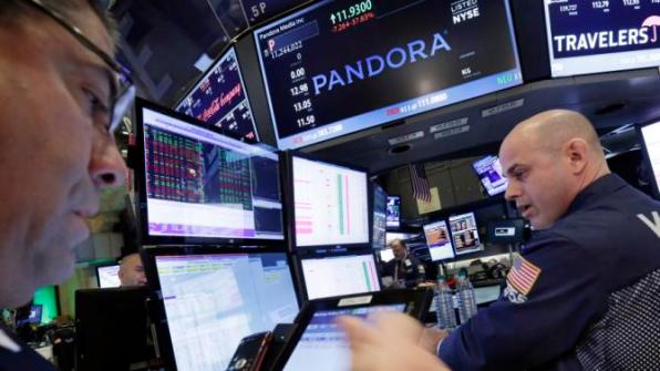 Specialist Mark Fitzgerald, right, works at the post on the floor of the New York Stock Exchange that trades Pandora, Friday, Oct. 23, 2015. Streaming music company Pandora has agreed to pay $90 million to settle a lawsuit brought by major record labels over its use of recordings released before 1972. (AP Photo/Richard Drew)